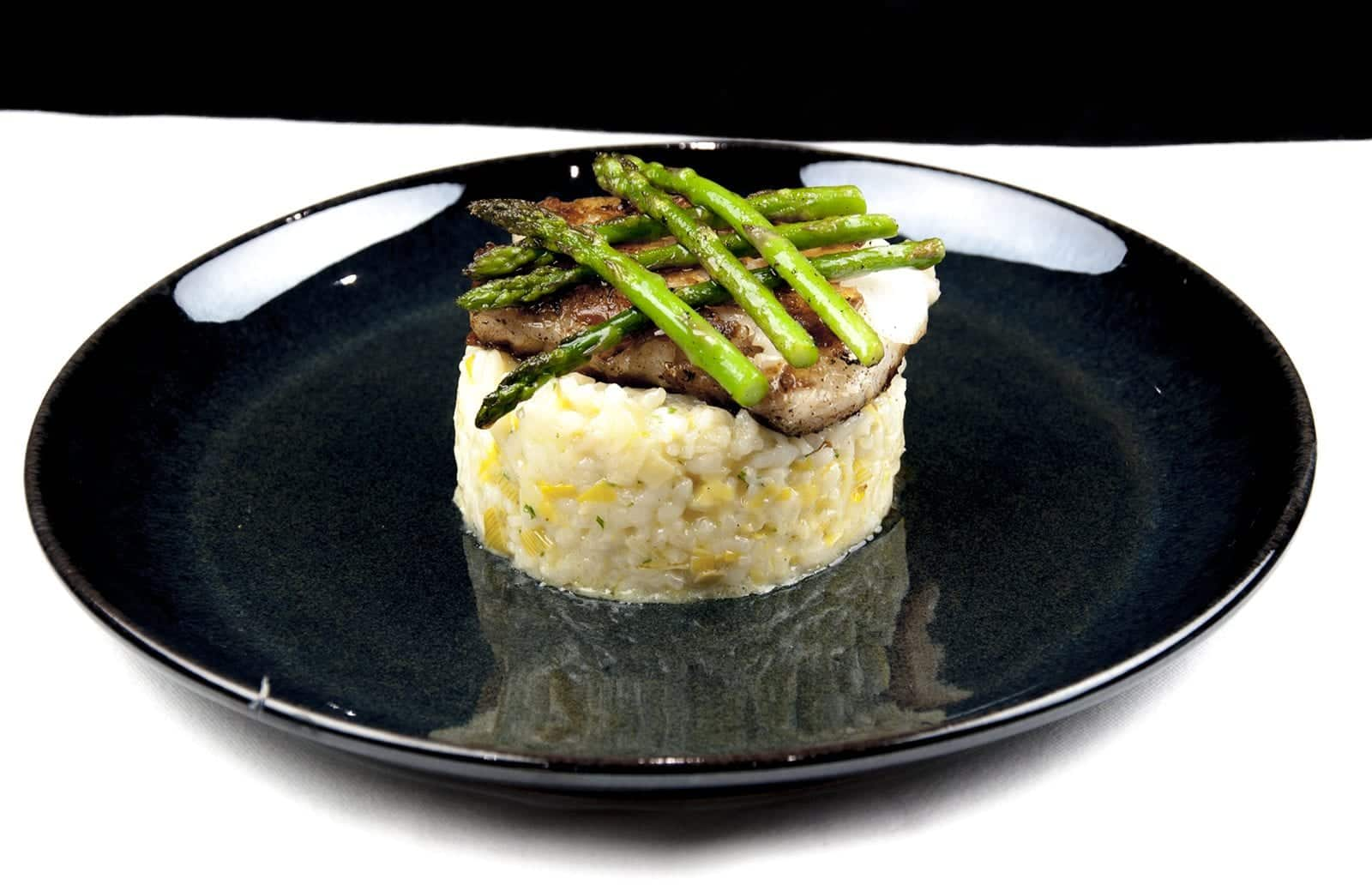Pan fried cod on a bed of leek risotto served with asparagus | theyumyumclub