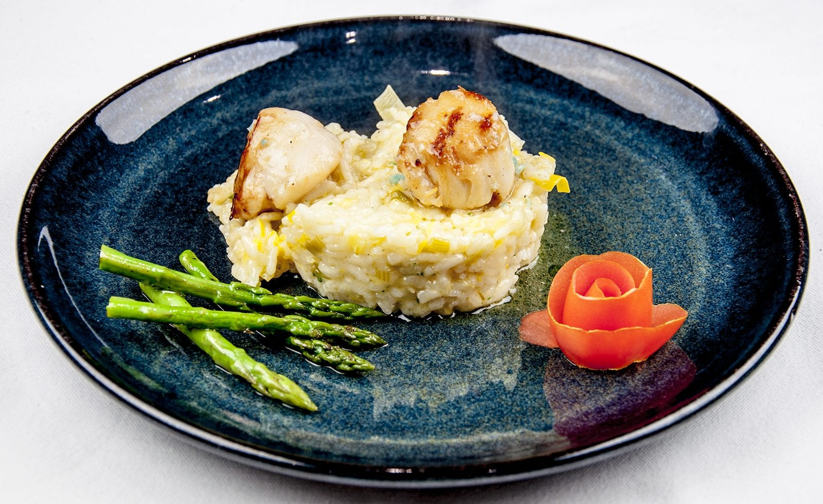Pan fried scallops on a bed of leek risotto served with asparagus and garnished with a tomato rose | theyumyumclub