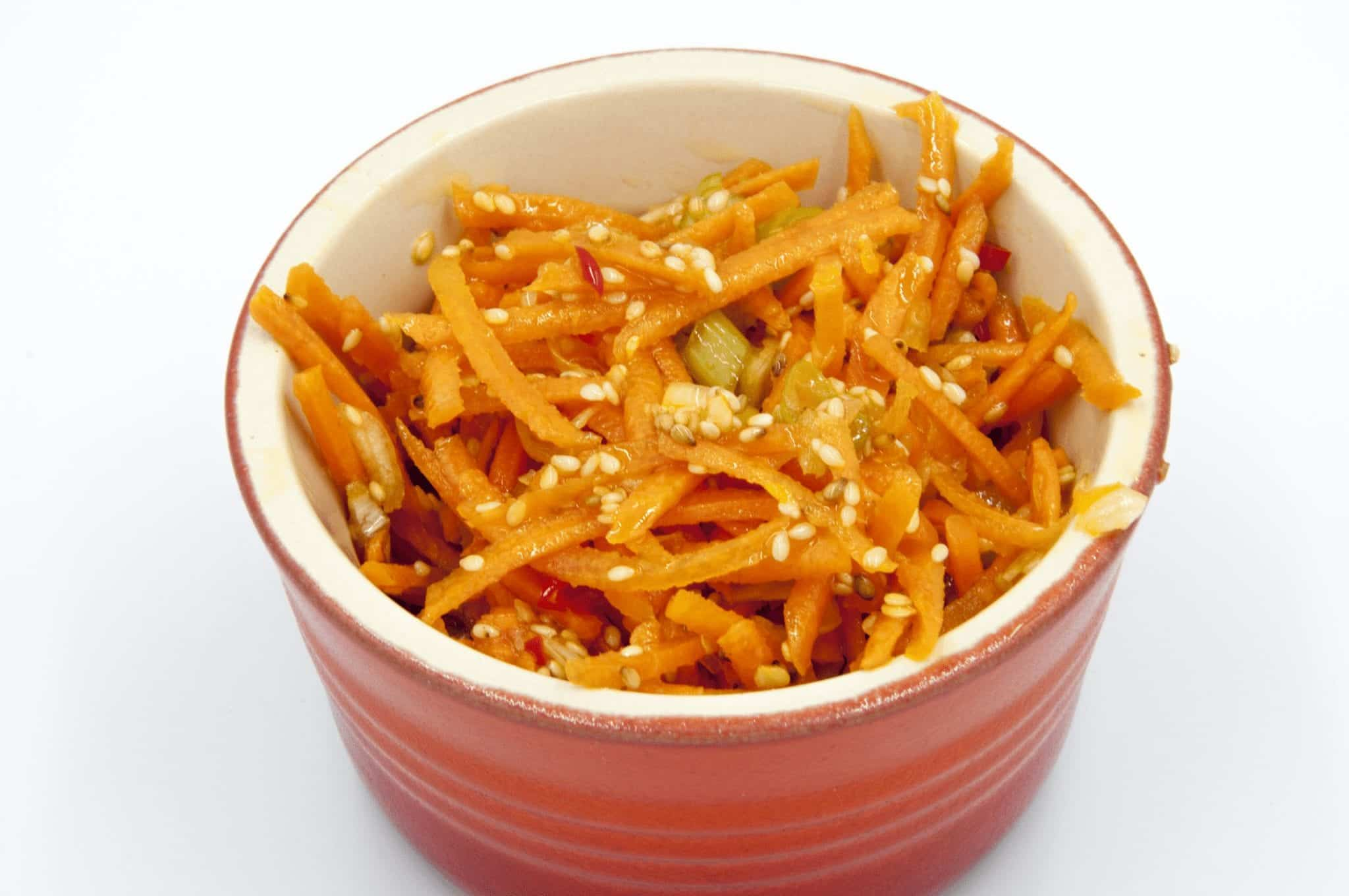 This spicy carrot, sesame and scallion salad is so simple and so healthy. 3 ingredients for the salad, 4 ingredeints for the spicy dressing, and just over 200 calories per bowl. Yum! | theyumyumclub.com