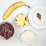 Raspberry and pineapple smoothie, with a little surprise! Banana to add texture and a wonderful hint of cinnamon to taste. A great start to the day. Yum! | theyumyumclub.com