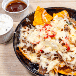 We all know pulled pork nachos but how about tangy pulled pork shoulder Doritos! Tangy cheese Doritos covered in spicy slow-cooked pork shoulder drowned in melted cheddar cheese. Yum! | theyumyumclub.com