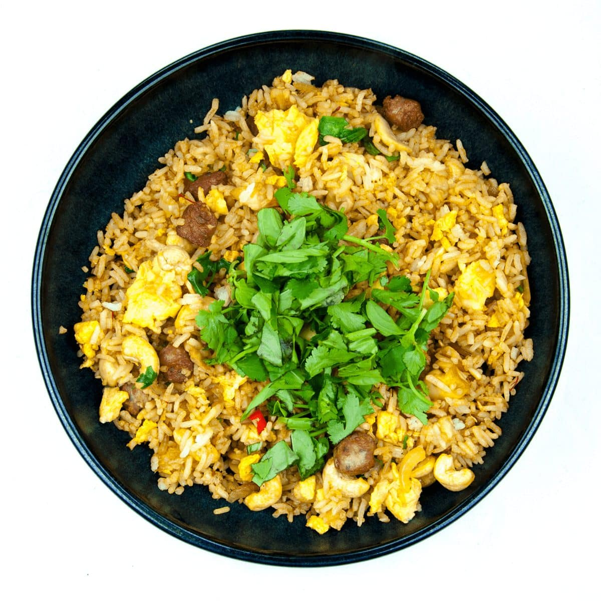 This Thai style sausage fried rice is a fusion of the best from East and West. Cashews, chilli, garlic, basil, coriander and sweet smelling saffron. Yum! | theyumyumclub.com